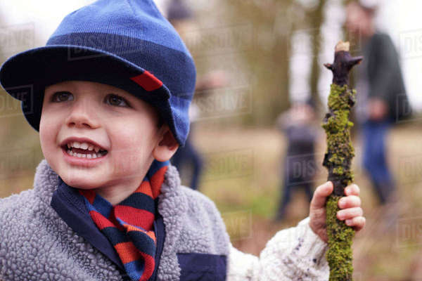 Young boy holding stick on family winter walk Royalty-free stock photo