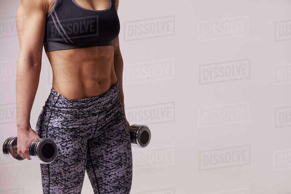 Dark haired young woman using dumbbells, mid section crop Royalty-free stock photo