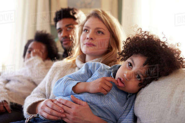 Family relaxing on sofa at home watching television together Royalty-free stock photo