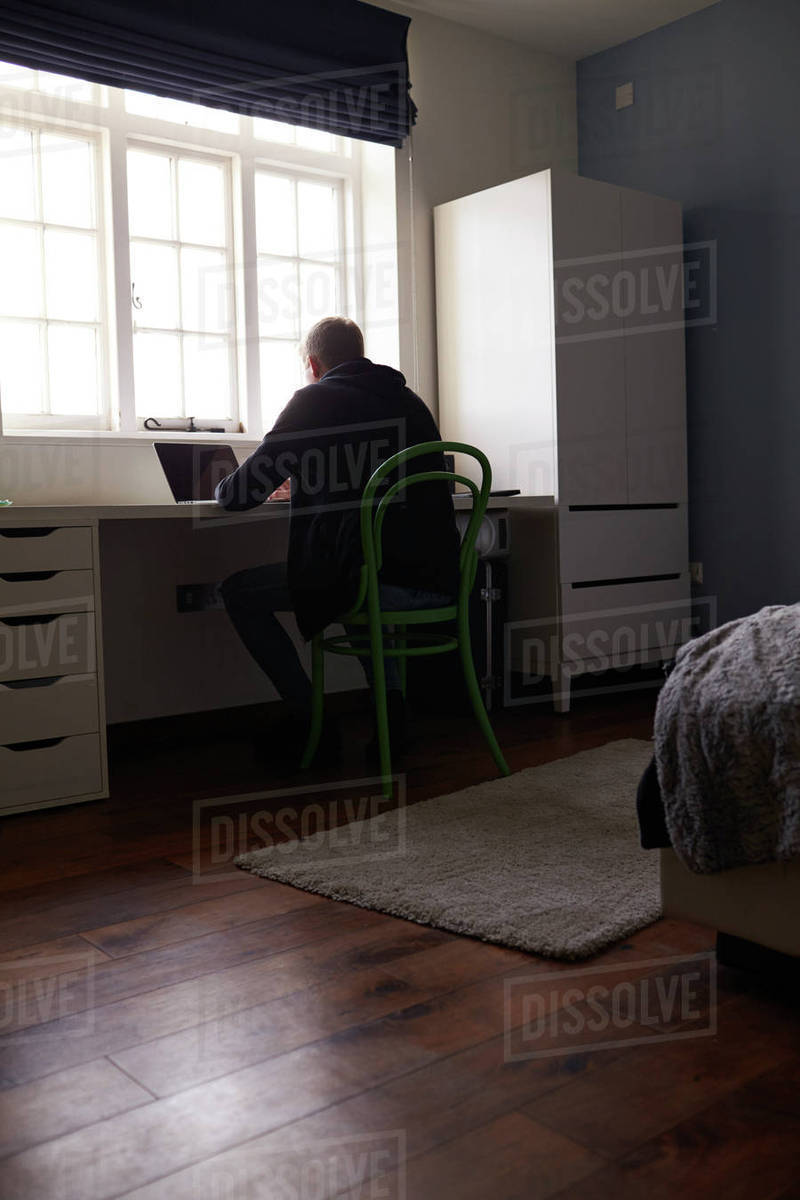 Teenage Boy Sitting At Desk In Bedroom Using Laptop Stock Photo
