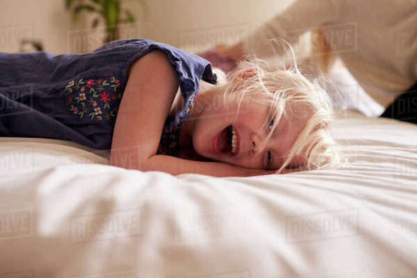 Portrait of young girl lying on parent's bed Royalty-free stock photo