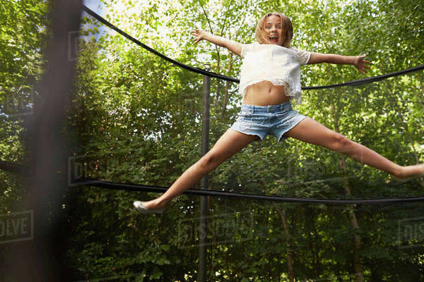 Girl does star jump on trampoline in a garden Royalty-free stock photo