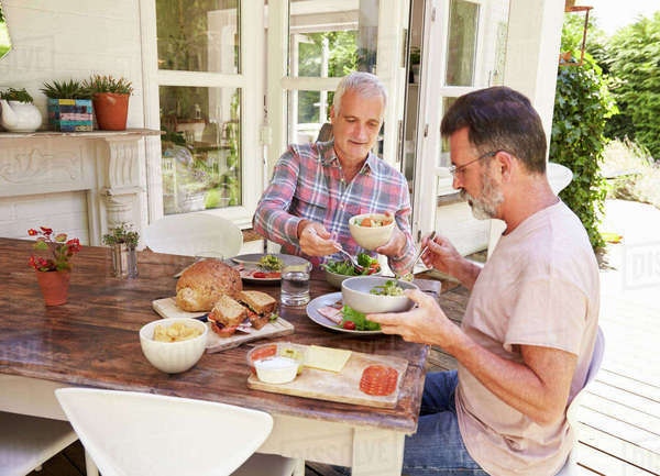 Gay male couple serving lunch on their patio, side view Royalty-free stock photo