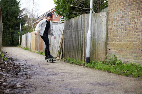 Young man skateboarding in an alley, low angle view Royalty-free stock photo