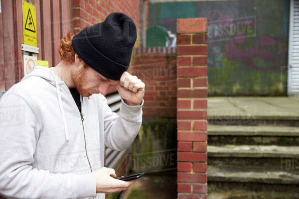 Waist up view of young man using phone in an urban setting Royalty-free stock photo