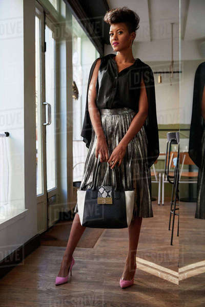 Stylish woman stands holding handbag in cafe, full length Royalty-free stock photo