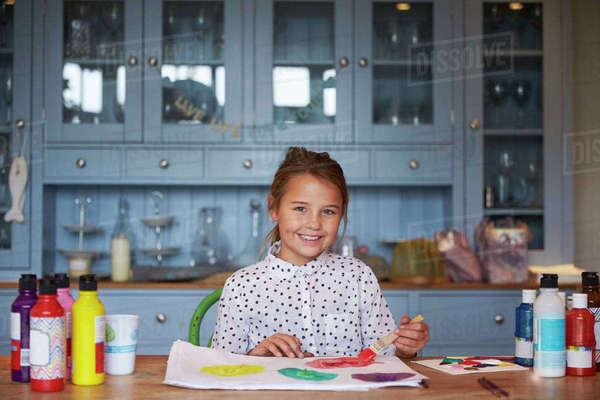 Portrait Of Smiling Girl At Kitchen Table Painting Picture  Royalty-free stock photo