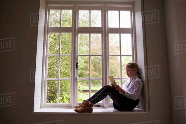 Girl Sits By Window At Home Using Digital Tablet Royalty-free stock photo