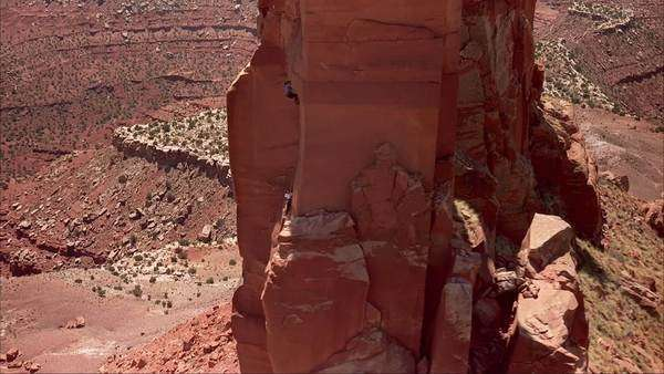Aerial shot of a two women climbing a cliff in a desert Rights-managed stock video