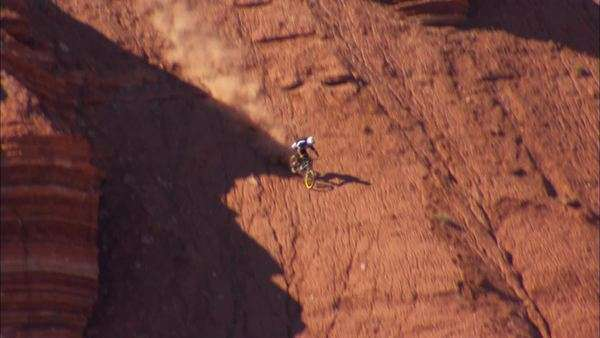 Tracking shot of a BMX biker riding down a high mountain Rights-managed stock video
