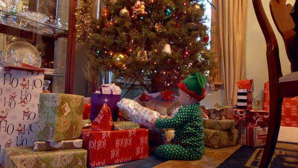 Static shot of a baby opening Christmas presents Rights-managed stock video