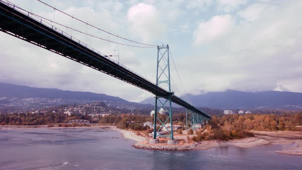 Locked-off shot of the Lions Gate Bridge from a moving boat with mountains in the background Rights-managed stock video