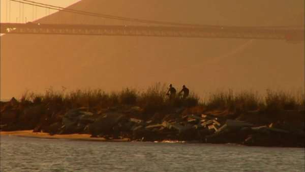 Tracking shot of two people riding bikes along breakwater in San Francisco Rights-managed stock video