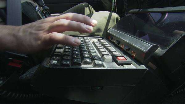 Close-up shot of a deputy officer inputting data into computer of a patrol car Rights-managed stock video