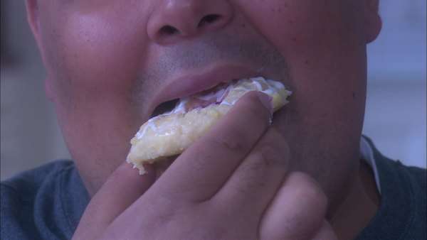 Close-up shot of an overweight man eating a sweet roll Rights-managed stock video