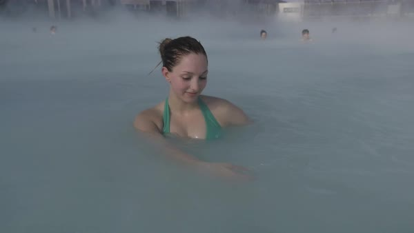 Medium shot of a woman bathing in a hot spring in slow motion Royalty-free stock video