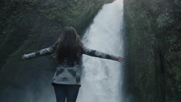 Slow motion shot of a woman extending her arms at a waterfall Royalty-free stock video