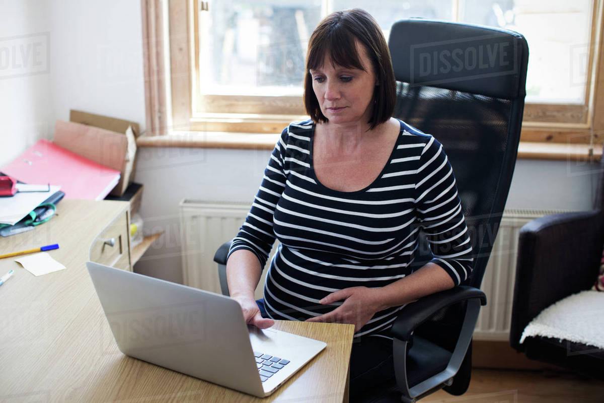 Mature pregnant woman working in home office