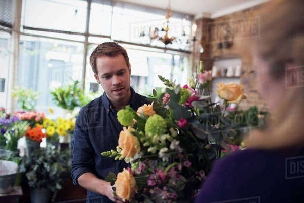 Florist serving male customer with roses in shop Royalty-free stock photo