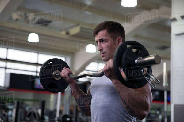 Young man lifting weights in gym Royalty-free stock photo