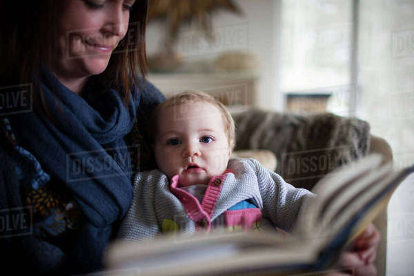 Grandmother reading story on sofa with baby granddaughter Royalty-free stock photo