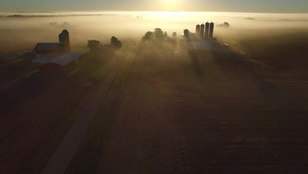 Flying over rural farms, fields, houses, on a foggy morning. Royalty-free stock video