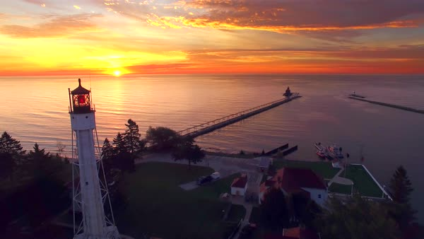 Amazing sunrise on Lake Michigan with not one, but two lighthouses, moving aerial perspective. Royalty-free stock video