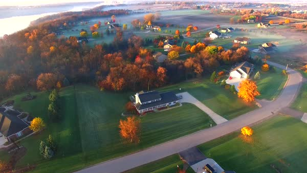 Colorful Autumn aerial flyover of scenic rural America neighborhood, a flock of geese flies through. Royalty-free stock video