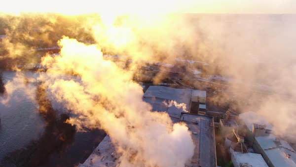 Aerial flyby of beautiful smokestack emissions illuminated in the sunrise. Royalty-free stock video