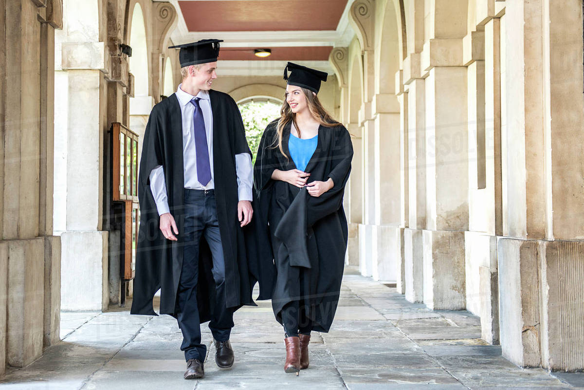 Two students in graduation gowns walking outside a building at ...