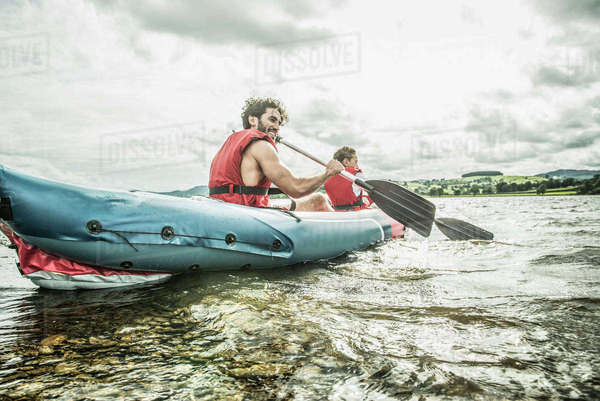 A man and a boy in a kayak paddling away from the shore on Bala Lake in Wales Royalty-free stock photo
