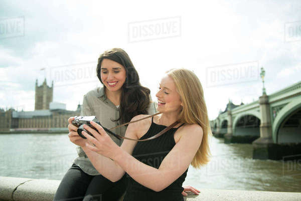 Two friends taking photographs on the South Bank in London with the Houses of Parliament in the background Royalty-free stock photo