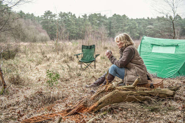Senior lady sitting enjoying the wilderness from her campsite Royalty-free stock photo