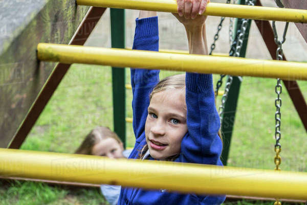 A ten year old girl in school uniform climbing on playground apparatus Royalty-free stock photo