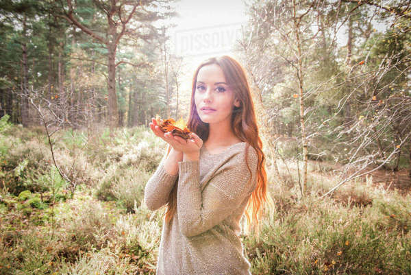 A young woman standing with a handful of leaves in a forest in Autumn Royalty-free stock photo