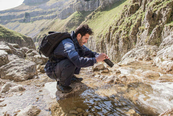 A mountaineer filling his water bottle from a mountain stream Royalty-free stock photo