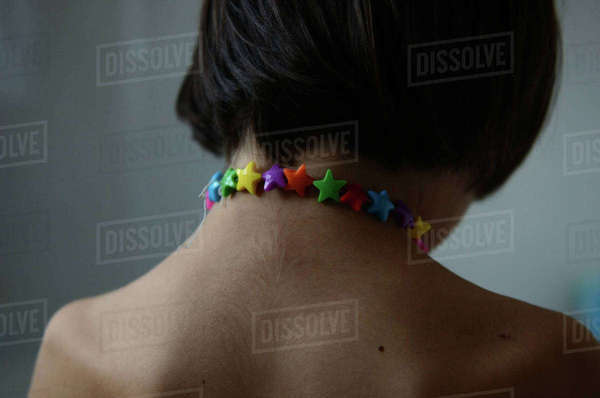 Back of child neck and shoulders wearing multi-coloured star necklace. New Zealand. November, 2013 Rights-managed stock photo