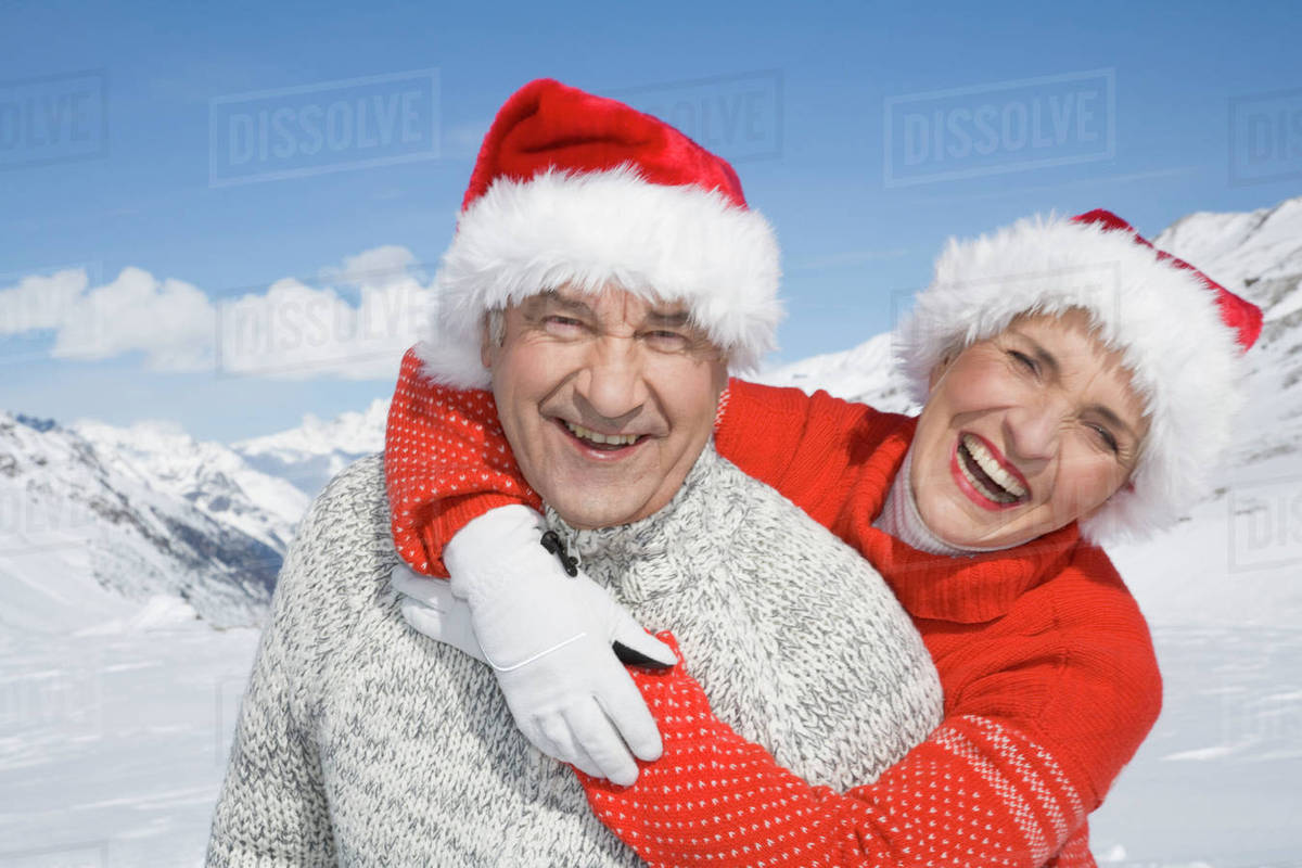 ec6d57272 Portrait of happy senior couple wearing Santa hats in mountains on winter  day stock photo