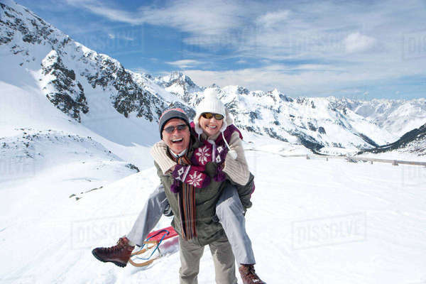 Portrait of smiling senior couple piggybacking on snowy mountain Royalty-free stock photo