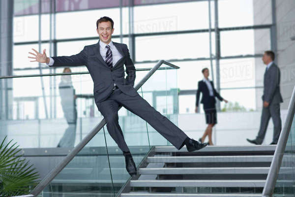 Portrait of enthusiastic businessman in suit sliding down railing in lobby Royalty-free stock photo