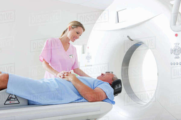 Technician nurse comforting and preparing patient for CT scan in hospital Royalty-free stock photo