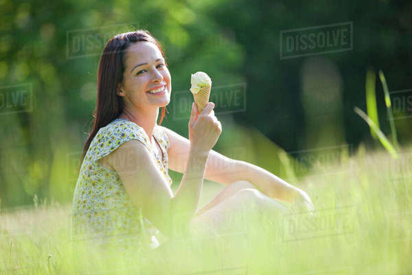 Portrait happy woman eating ice cream cone in sunny summer grass Royalty-free stock photo