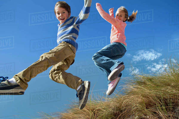 Exuberant brother and sister jumping for joy over grass Royalty-free stock photo