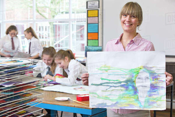 Portrait smiling art teacher showing painting in art class Royalty-free stock photo
