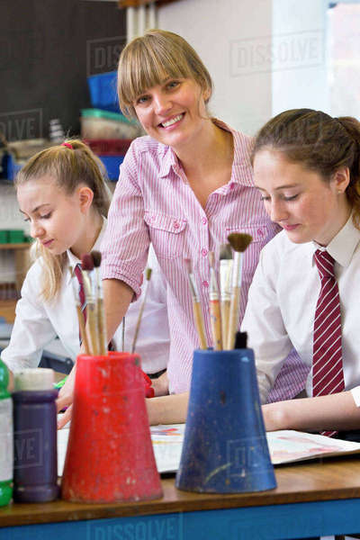 Portrait confident art teacher teaching middle school students painting in art class Royalty-free stock photo