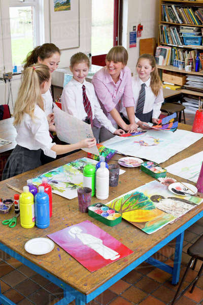 Art teacher painting with middle school students in art class Royalty-free stock photo