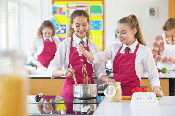 High school students cooking pasta in home economics class Royalty-free stock photo