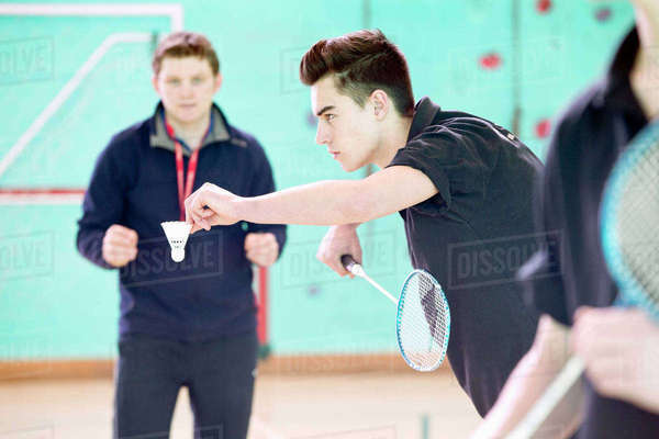 Focused high school student playing badminton in gym class Royalty-free stock photo