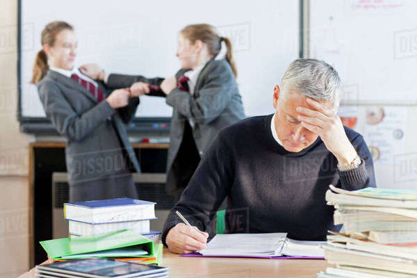 Teacher trying to grade homework with students fighting in background Royalty-free stock photo