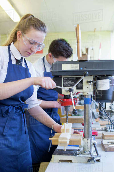 Female high school student using drill in woodworking class Royalty-free stock photo